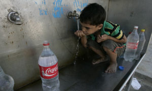 Water in Gaza : A Palestinian boys drinks water from a public tap in Gaza